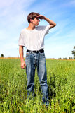 Teenager in field. The teenager inspects area in the field Royalty Free Stock Photo