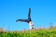 Teenager in the field. Somersault on the summer meadow stock photography