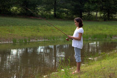 Teenager fishing on river Stock Image