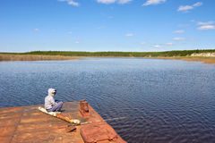 Teenager is fishing. Sitting on old barge stock image