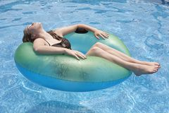 Teenager floating on float in pool royalty free stock images