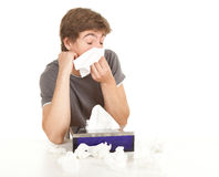 Teenager with flu blowing her nose Stock Image