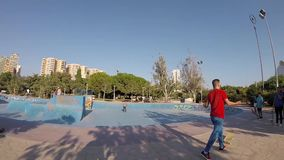 Teenager Flying on Skateboard in Skatepark Bowl. Kids Riding a Skateboard And Jumping Air Trick in Skatepark Bowl of Turia River Park, Valencia, Spain, Europe stock footage