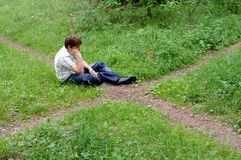 Teenager in forest by crossroad choose the path Stock Images