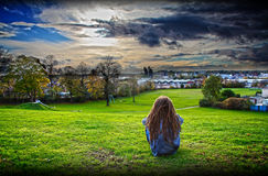 Teenager in foster care. Grungy teenager with dreadlocks sitting on a hill contemplating life in foster care Stock Photo