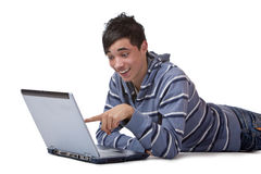 Teenager found something funny on internet. Young teenager is lying on floor and pointing on display of his laptop and smiles. Isolated on white stock images