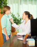 Teenager in front of a doctor. Male teenager in front of a female doctor with stethoscope in clinic Stock Photo