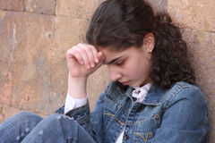 Teenager girl. Thinking teenager girl on wall background-2 Royalty Free Stock Image
