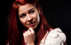 Teenager girl. Young woman smiling and thinking on black background Stock Photo