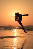 Teenager girl in active gymnastic workout during sunset. Teenager gymnast girl doing - workout on the beach at sunset time. Girl enjoying active workout royalty free stock photography