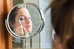 Teenager girl looking her self in a round mirror applying eyeshadow with a brush. royalty free stock photos
