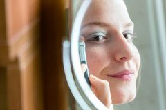 Teenager girl looking her self in a round mirror applying eyeshadow with a brush. royalty free stock photo