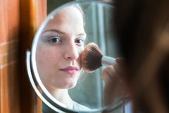 Teenager girl looking her self in a mirror applying powder to he royalty free stock image