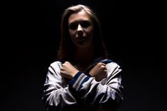 Teenager girl with arms crossed on her chest. Serious teenager girl in shadow - photo portrait Royalty Free Stock Image