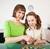Teenager girl assembling jigsaw with her mother Stock Images