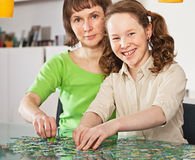 Teenager girl assembling jigsaw with her mother Royalty Free Stock Photography