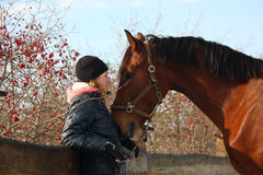 Teenager girl and bay horse hugging each other Stock Photos