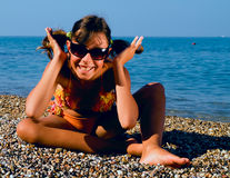 Teenager girl on the beach. The girl, a teenager in a playful pose. The girl smiles. The hair gathered in a ponytail.Girl in sunglasses Royalty Free Stock Photography