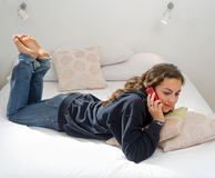 Teenager girl bed cell phone Stock Photo