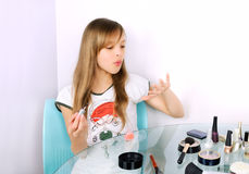 Teenager girl blowing on painted nails horizontal Royalty Free Stock Photos