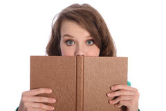 Teenager girl with blue eyes reading a book. Teenager girl with big blue eyes wide open in surprise from reading a book Stock Images