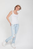 Teenager Girl in blue jeans, white shirt and white sport shoes p. Osing Stock Photography