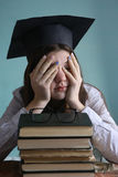Teenager girl with book pile and graduation cap tired eyes Royalty Free Stock Image