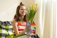 Teenager girl with bouquet of yellow spring flowers, smiling and happy sitting at home in bed.  royalty free stock photos