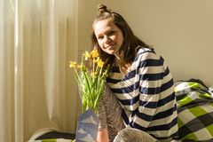 Teenager girl with bouquet of yellow spring flowers, smiling and happy sitting at home in bed.  royalty free stock photography