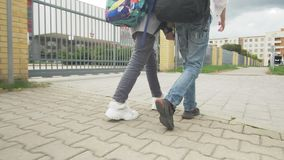 Teenager Girl and Boy walking to school on the sidewalk with a backpack . Close-up of feet. Slow motion video.