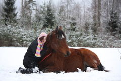 Teenager girl and brown horse lying in the snow Stock Images