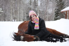 Teenager girl and brown horse lying in the snow Stock Photography