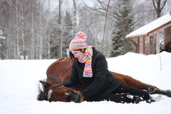 Teenager girl and brown horse lying in the snow Stock Image