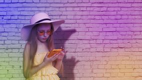 Teenager girl browsing mobile phone on brick wall background in colorful light. Young girl using smartphone for surfing. In social networks on multicolored stock video footage