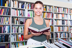 Teenager girl brunete looks for the right book in library Stock Photos