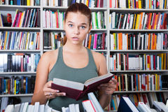 Teenager girl brunete looks for the right book in library Stock Image