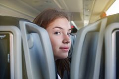 teenager girl is in the bus travelling sitting on the seat looking at the camera between the seats stock image
