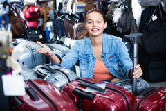 Teenager girl buying large wheeled plastic luggage bag Stock Images