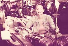 Teenager girl buying large wheeled plastic luggage bag Royalty Free Stock Photos