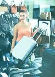 Teenager girl buying large wheeled plastic luggage bag Stock Image