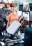 Teenager girl buying large wheeled plastic luggage bag Royalty Free Stock Image