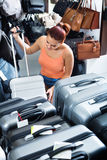 Teenager girl buying large wheeled plastic luggage bag Royalty Free Stock Image