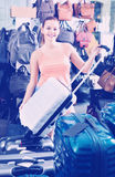 Teenager girl buying large wheeled plastic luggage bag Royalty Free Stock Photos