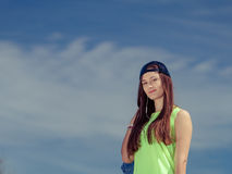 Teenager girl in cap listening to music outdoor. Stock Photos