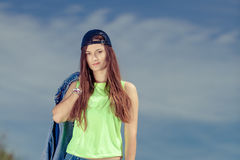 Teenager girl in cap listening to music outdoor. Stock Photo