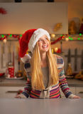 Teenager girl in christmas decorated kitchen looki Stock Photos