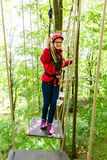 Teenager girl climbing in high rope course or parl Royalty Free Stock Photo