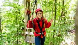Teenager girl climbing in high rope course or parlor Royalty Free Stock Photos