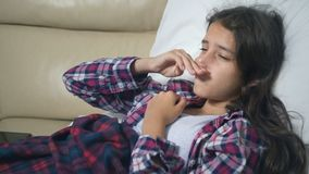 Teenager girl with a cold blows her nose lying on the sofa under the covers. stock footage
