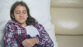 Teenager girl with a cold blows her nose lying on the sofa under the covers. stock video footage